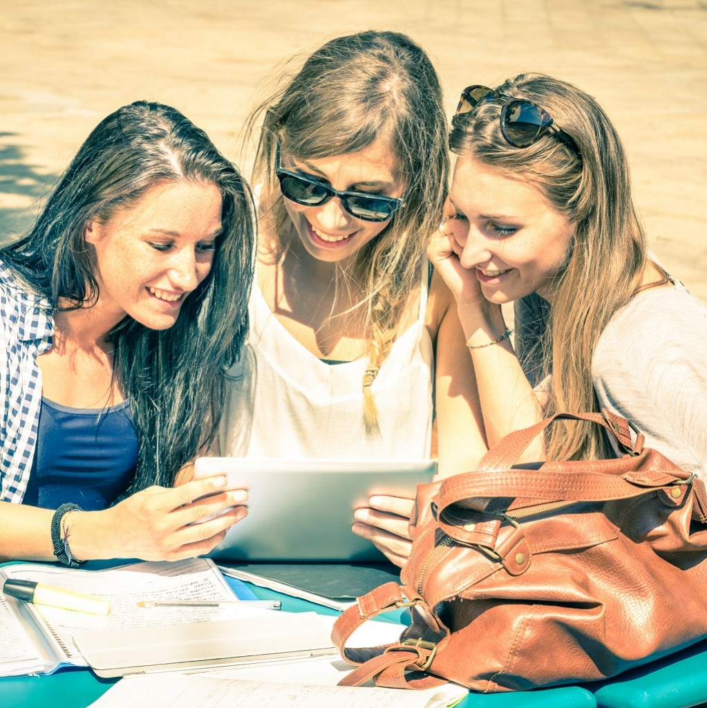 Young hipster girlfriends studying and having fun together with tablet - Social interaction on new technology trends and internet connection in everyday lifestyle - Overexposed vintage filtered look